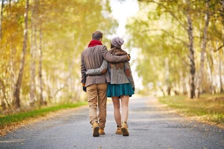 caminando: Vista posterior de la joven pareja caminando en el parque en otoño