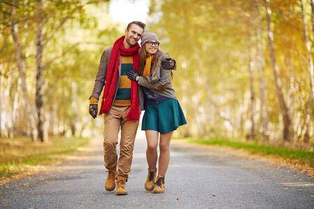 persona caminando: Pareja joven con estilo disfruta de la caminata en el parque