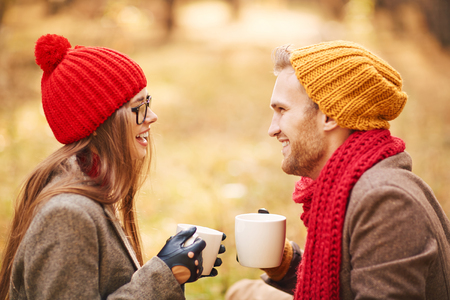 amorous: Amorous young couple with cups of tea talking outdoors