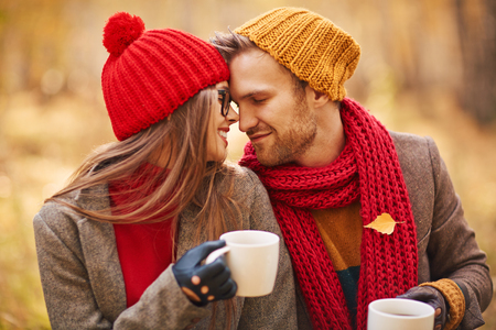 amorous woman: Amorous young couple in stylish casualwear holding cups of tea