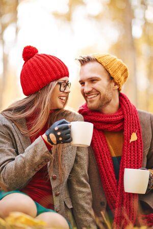 femme romantique: Amoureuse jeune couple parlant et riant tout en buvant du thé dans l'environnement naturel Banque d'images