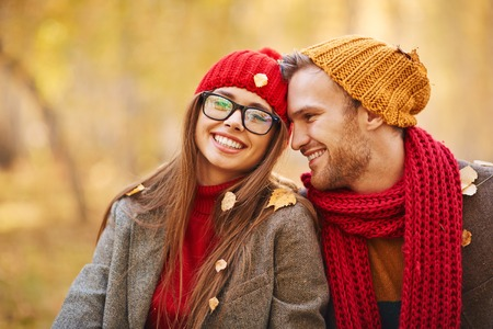 amorous woman: Happy young couple looking at camera during leaf fall