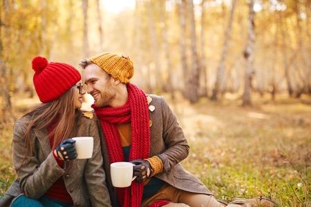 parejas amor: pareja moderna en chaquetas y gorras tomando el té en el ambiente natural