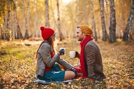 restful: Restful couple in warm clothes enjoying outdoor tea in park