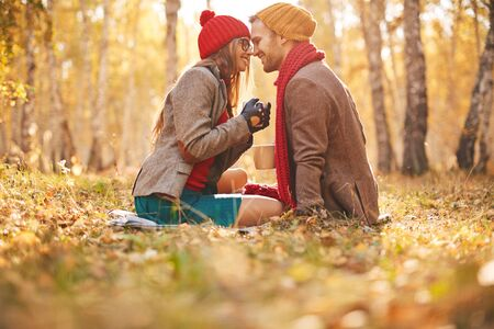 sweethearts: Affectionate sweethearts sitting face to face on autumn leaves Stock Photo