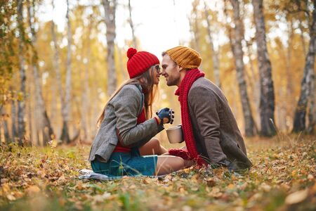 Sweethearts sitting face to face in park in autumn