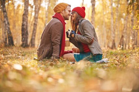 Affectionate guy and girl sitting face to face in natural environment