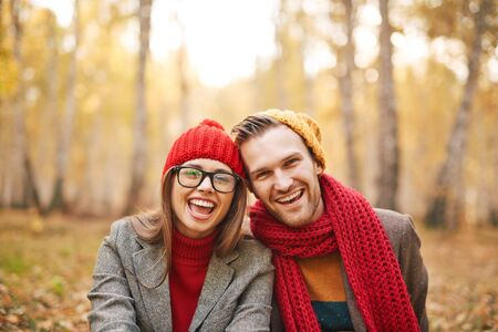 ecstatic: Ecstatic young dates in warm jackets and knitted caps looking at camera outdoors Stock Photo