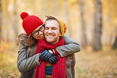 gloved: Joyful girl embracing her boyfriend in park
