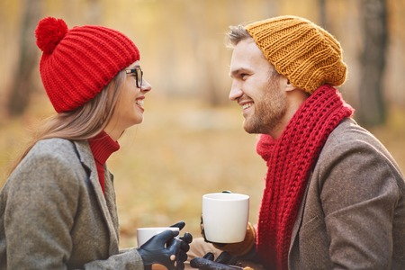 Joyful young couple talking outdoors while having tea