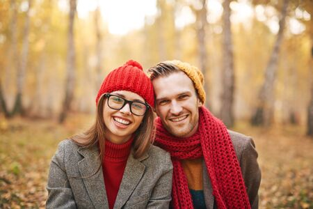 sweethearts: Stylish sweethearts in casualwear looking at camera in park Stock Photo