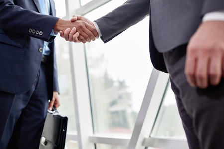 career man: Hands of businessmen during handshake Stock Photo