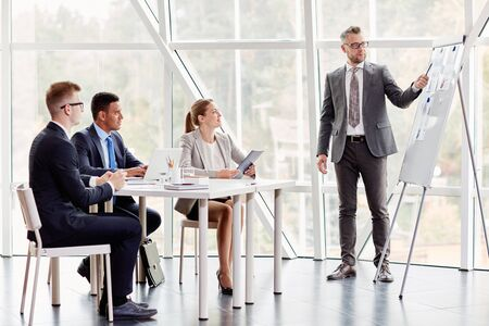 business education: Confident businessman pointing at document on board while explaining his idea to colleagues in office