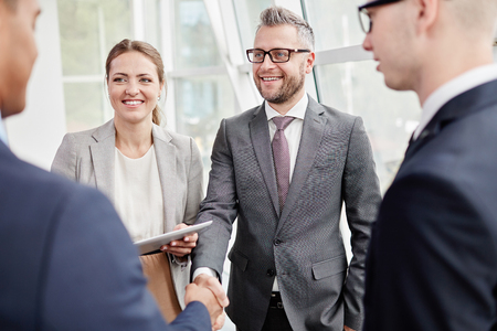 agreement: Happy colleagues looking at their business partner while greeting him