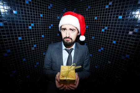 dissatisfied: Dissatisfied businessman with giftbox looking at camera in night club