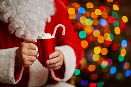 cups of coffee: Tasty latte with whipped cream and candy cane in Santa hands