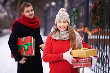 adult christmas: Happy woman with Christmas presents looking at camera on background of her husband outdoors Stock Photo