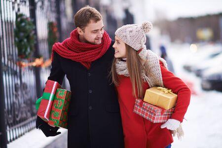 pareja en casa: Pareja joven con giftboxes hablando mientras caminaba hacia su casa en la víspera de Navidad