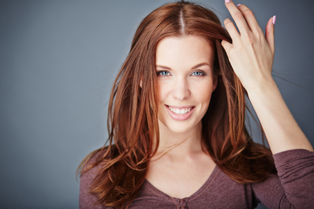 hair style: Young woman with long hair looking at camera with smile