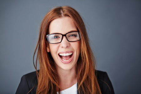 ecstatic: Ecstatic young businesswoman in eyeglasses looking at camera