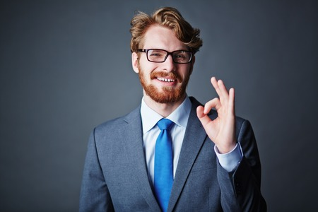 Happy businessman in eyeglasses and suit showing okay sign