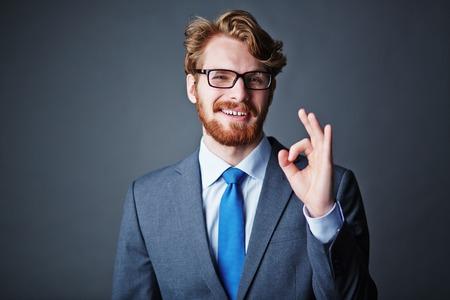 persona feliz: Feliz hombre de negocios en gafas y traje que muestra signo bien Foto de archivo