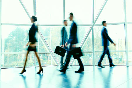 hurrying: Blurred figures of hurrying employees inside office building