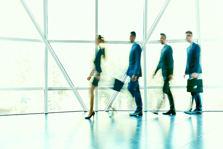 hurrying: Row of hurrying business people moving along window inside office building