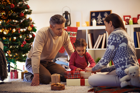 christmastide: Family of three packing gifts and tying knots on tops of boxes before Christmas