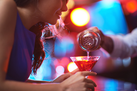 young people party: Girl looking at drink in martini glass while barman pouring cocktail for her Stock Photo