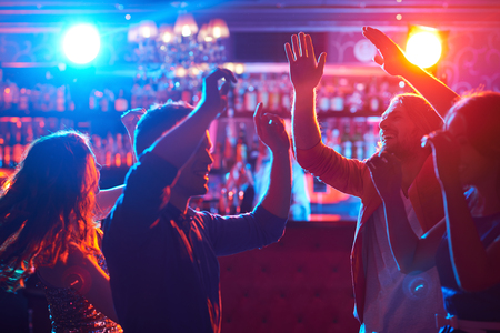 restaurant people: Happy friends dancing at party in bar Stock Photo