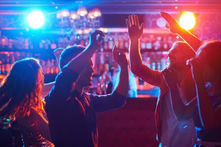 människor: Lyckliga vänner dansar på fest i bar Stockfoto