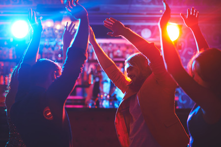 club: Happy friends with raised arms dancing at night club Stock Photo