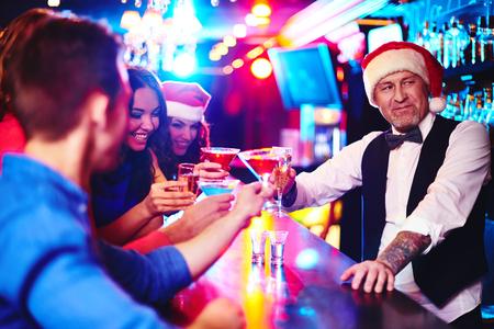 barman: Happy company cheering up by counter with barman in Santa cap near by Stock Photo
