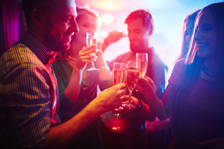 champagne flutes: Group of happy friends toasting at party with champagne Stock Photo