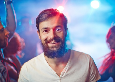 unshaven: Happy unshaven man looking at camera with smile during party in night club