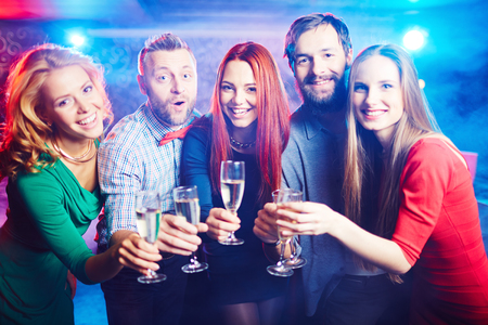 holiday gathering: Group of ecstatic friends having party in night club Stock Photo