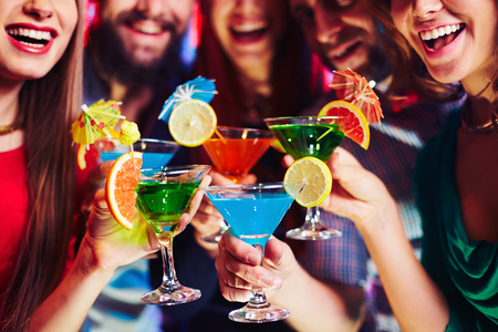 saúde: Amigos alegres com os cocktails cítricas torcendo na festa