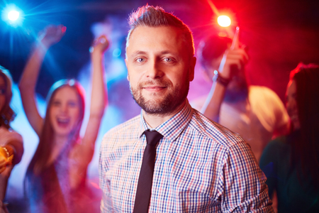 party friends: Handsome man looking at camera at party on background of dancing freinds