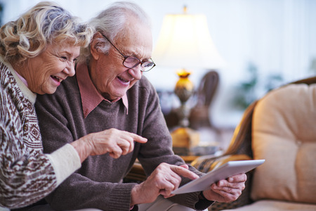 touchpad: Happy senior couple using touchpad at home