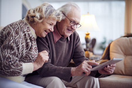 Happy aged couple with touchpad networking at home