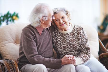 Homem sênior feliz e mulher que têm o descanso em casa