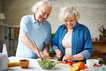 Happy senior couple preparing fresh vegetable salad in the kitchen
