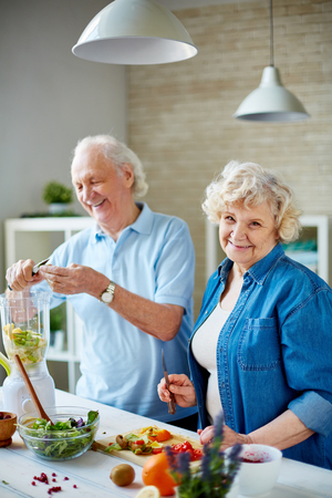 Portrait couple: Happy seniors cooking vegetarian food in the kitchen