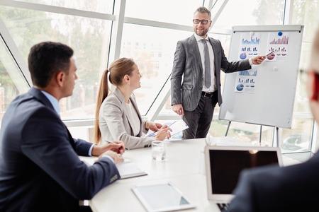 Hombre de negocios confidente por pizarra que muestra los datos sobre las ventas en el mercado a sus colegas