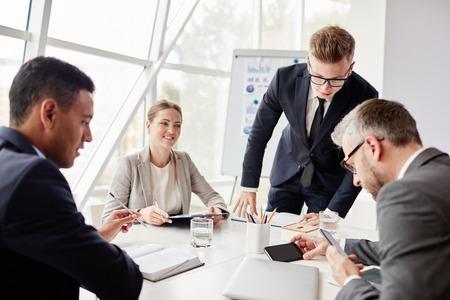 trabajo en equipo: Dos hombres de negocios que buscan en los datos en los teléfonos celulares con sus colegas cerca por
