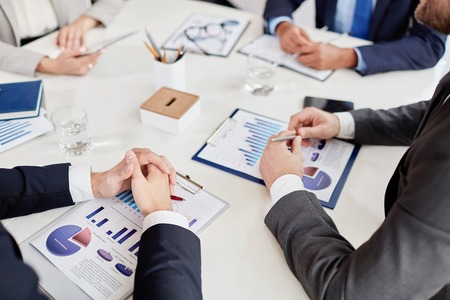 Hands of employee on business paper at workplace during meeting Stock Photo