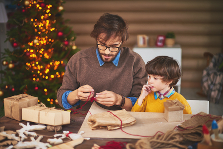dad son: Young man preparing thread for tying xmas gifts with his son near by