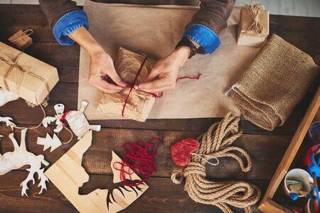 juguetes de madera: Manos del hombre atando navidad regalo envuelto en papel