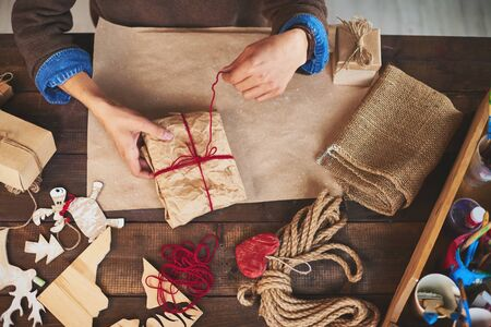 gifts: Hands of man tying up wrapped gift with woolen thread